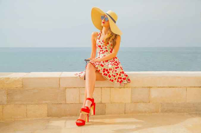 woman in red and white floral dress wearing brown sun hat